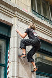 Man climbing a house wall on street boulder contest Royalty Free Stock Image