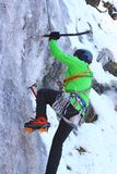 Man climbing an ice wall. Man in green jacket climbing an ice wall - motion blur on ice ax Stock Photography