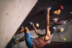 Man climbing indoor boulder wall. Athletic man bouldering at an indoor climbing centre. Professional climber climbing wall upside down at an indoor climbing gym stock photography