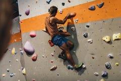 Man climbing indoor boulder wall. Man bouldering at an indoor climbing centre. Climber practicing rock climbing at an indoor climbing gym stock image