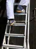 Man is climbing a ladder Stock Image