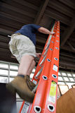 Man Climbing a Ladder. A young worker climbing up a ladder to enter through the hatch door in the ceiling. Slight motion blur showing movement up the rungs stock images
