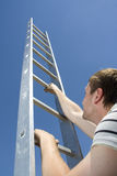 Man climbing ladder stock photo