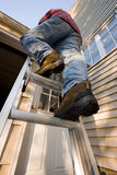 Man Climbing Ladder. Up to the roof of a house Stock Image
