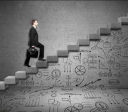 Man climbing ladder with business drawings Royalty Free Stock Photography