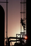 Man climbing ladder at gas refinery. With sunburst Royalty Free Stock Image