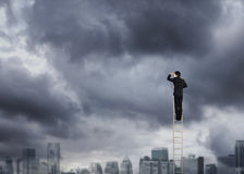 Man climbing on a ladder over a city looking ahead Stock Photography