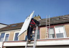 Man climbing the ladder with solar panel Royalty Free Stock Image