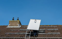 Man climbing the ladder with solar panel royalty free stock photography