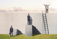 Man climbing on ladder on wall Stock Photos