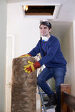 Man Climbing Into Loft To  Insulate House Roof Stock Image