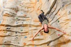 Man climbing on man-made cliff Stock Photos