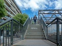 Man climbing metal ladder royalty free stock photo