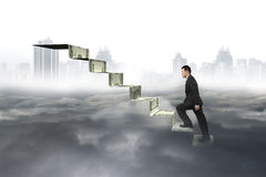 Man climbing on money stairs with cityscape cloudscape Stock Photos