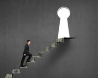 Man climbing on money stairs to key hole Stock Photo