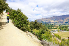Man is climbing on the mountain with little girl on the shoulders. lake Wanaka town. New Zealand Stock Images