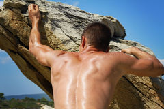 Man climbing on mountain rocks. Close up on muscular back and hands. Extreme sports outdoors. Active summer vacation Royalty Free Stock Image