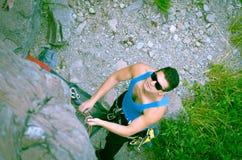Man climbing mountain with sunglasses Stock Photos