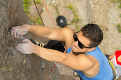 Man climbing mountain with sunglasses Stock Photography