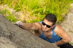 Man climbing mountain with sunglasses Royalty Free Stock Photography