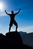 Man climbing in mountains arms outstretched. Man climbing in mountains, success concept Stock Image