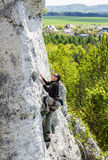 Man climbing natural rocky wall. Man climbing natural rocky wall with panoramic view below stock photo