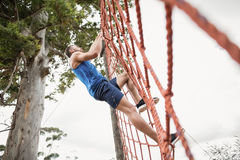 Man climbing a net during obstacle course. In boot camp Royalty Free Stock Photos