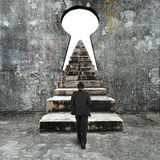 Man climbing old concrete stairs toward keyhole Stock Images