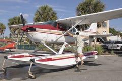 Man climbing onto seaplane Royalty Free Stock Photos