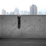 Man climbing over wall with business doodles Royalty Free Stock Photography