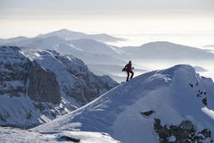 Man climbing a peak with snowboard. Young man with snowboard in beautiful winter landscape - Bucegi mountains, Romania Royalty Free Stock Photography