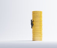 Man climbing a pile of coins Royalty Free Stock Photography