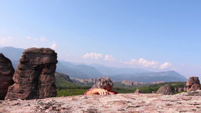 Man is climbing a rock and sitting to admire the beautiful Belogradchik valley stock video