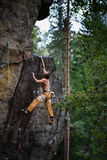 Man is climbing on rock. Success climbing, reaching the top Adrenalin, strength, ambition. Stock Images
