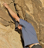 Man climbing a rock wall. Athletic man, climbing a rock, reaching out his hand to get a good grip Stock Photography