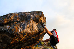 Man climbing on rock.  Young fit, strong male climber Stock Images