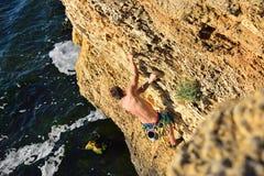 Man climbing on a rock Royalty Free Stock Photos