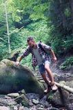 Man climbing rocks on mountains river Stock Image