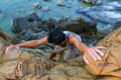 Man climbing the rocks near the sea. Royalty Free Stock Images