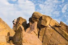 Man climbing a rocky mountain peak Stock Images