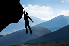 Man Climbing On Rocky Mountain. Silhouette Of A Man Climbing On Rocky Mountain Royalty Free Stock Images