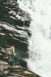 Man climbing rocky mountains with waterfall outdoor. Travel Lifestyle success concept adventure scandinavian vacations extreme sport Royalty Free Stock Photography