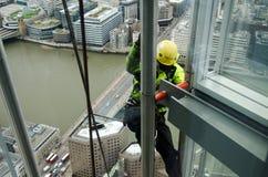 Man climbing The Shard, London. LONDON, ENGLAND - FEBRUARY 6: Construction worker climbing the outside of The Shard in London on February 6 2013.  The recently Stock Photo