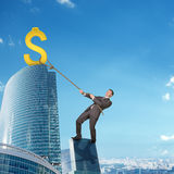 Man climbing skyscraper with dollar sign Royalty Free Stock Image
