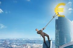 Man climbing skyscraper with euro sign Stock Image