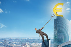 Man climbing skyscraper with euro sign Royalty Free Stock Image