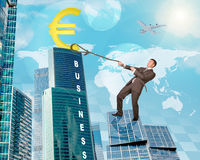 Man climbing skyscraper with euro sign Stock Photo