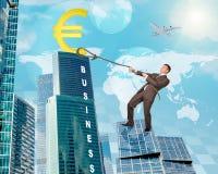 Man climbing skyscraper with euro sign Stock Photo