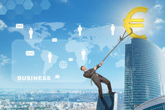 Man climbing skyscraper with euro sign Stock Images
