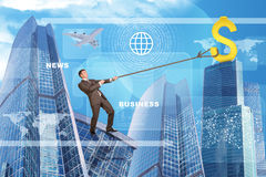 Man climbing skyscraper with world map. Businessman climbing skyscraper holding golden dollar sign Stock Photo